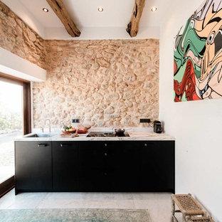 Foto de cocina lineal, mediterránea, pequeña, abierta, sin isla, con armarios con paneles lisos, puertas de armario negras, salpicadero beige y suelo de cemento