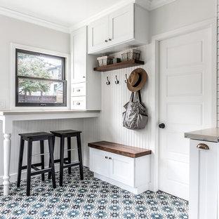 ロサンゼルスの中サイズのカントリー風おしゃれなキッチン (白いキャビネット、大理石カウンター、白いキッチンパネル、セラミックタイルのキッチンパネル、白い調理設備、セメントタイルの床、アイランドなし、マルチカラーの床、エプロンフロントシンク、シェーカースタイル扉のキャビネット) の写真