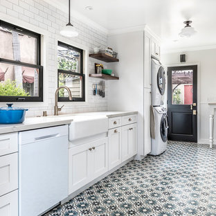 Mid-sized country galley separate kitchen in Los Angeles with white cabinets, marble benchtops, white splashback, ceramic splashback, white appliances, cement tiles, no island, multi-coloured floor, a farmhouse sink and shaker cabinets.