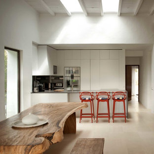 Inspiration for a mid-sized mediterranean u-shaped eat-in kitchen in London with flat-panel cabinets, white cabinets, stainless steel appliances, a peninsula and ceramic floors.