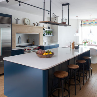 Inspiration for a large traditional kitchen/diner in Other with shaker cabinets, blue cabinets, quartz worktops, white splashback, marble splashback, stainless steel appliances, medium hardwood flooring, an island, white worktops and a submerged sink.