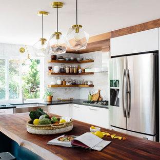 Idéer för funkis svart l-kök, med en rustik diskho, släta luckor, vita skåp, träbänkskiva, vitt stänkskydd, rostfria vitvaror, mellanmörkt trägolv, en köksö och brunt golv