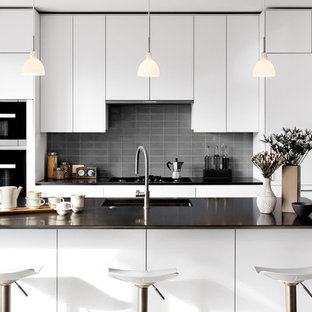 Modern kitchen appliance - Minimalist light wood floor kitchen photo in DC Metro with an undermount sink, flat-panel cabinets, white cabinets, quartz countertops, gray backsplash, an island, glass tile backsplash and black appliances