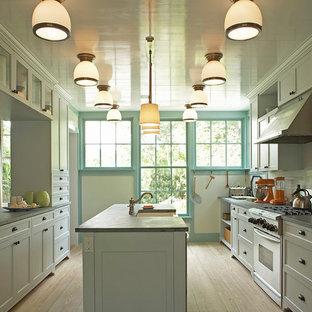 ニューヨークのトラディショナルスタイルのおしゃれなII型キッチン (エプロンフロントシンク、シェーカースタイル扉のキャビネット、白いキャビネット、白いキッチンパネル、サブウェイタイルのキッチンパネル、シルバーの調理設備) の写真