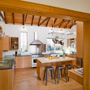 Eat-in kitchen - cottage u-shaped light wood floor eat-in kitchen idea in San Francisco with stainless steel appliances, a farmhouse sink, medium tone wood cabinets, metallic backsplash and an island