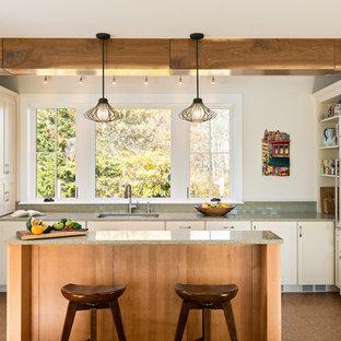 Cette photo montre une cuisine nature de taille moyenne avec un évier encastré, un placard à porte shaker, des portes de placard blanches, un plan de travail en verre recyclé, un électroménager encastrable, un sol en liège et un îlot central.