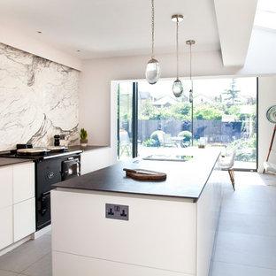Zweizeilige, Große Moderne Wohnküche mit Doppelwaschbecken, flächenbündigen Schrankfronten, Küchenrückwand in Weiß, Rückwand aus Marmor, Küchengeräten aus Edelstahl, Kücheninsel, weißem Boden und schwarzer Arbeitsplatte in London