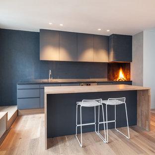 Foto de cocina lineal, nórdica, con armarios con paneles lisos, puertas de armario azules, encimera de madera, salpicadero azul, suelo de madera clara y una isla