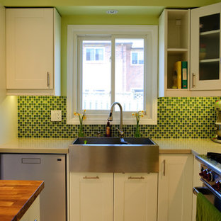 Contemporary l-shaped kitchen in Toronto with a belfast sink, shaker cabinets, green splashback, mosaic tiled splashback and stainless steel appliances.