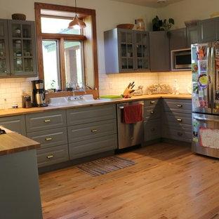 Mittelgroße Klassische Wohnküche in U-Form mit Schrankfronten im Shaker-Stil, grauen Schränken, Arbeitsplatte aus Holz, Küchenrückwand in Weiß, Rückwand aus Metrofliesen, Küchengeräten aus Edelstahl, braunem Holzboden, Kücheninsel, braunem Boden und brauner Arbeitsplatte in Minneapolis