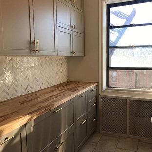 ニューヨークの中サイズのエクレクティックスタイルのおしゃれなキッチン (アンダーカウンターシンク、シェーカースタイル扉のキャビネット、グレーのキャビネット、木材カウンター、グレーのキッチンパネル、大理石のキッチンパネル、シルバーの調理設備、コンクリートの床、アイランドなし、グレーの床、茶色いキッチンカウンター) の写真