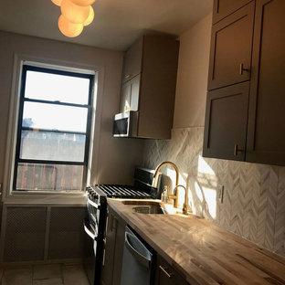 ニューヨークの中サイズのエクレクティックスタイルのおしゃれなキッチン (アンダーカウンターシンク、シェーカースタイル扉のキャビネット、グレーのキャビネット、木材カウンター、グレーのキッチンパネル、大理石の床、シルバーの調理設備の、コンクリートの床、アイランドなし、グレーの床、茶色いキッチンカウンター) の写真