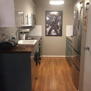 Foto di una piccola cucina parallela minimal chiusa con lavello da incasso, ante lisce, ante turchesi, top in legno, paraspruzzi bianco, paraspruzzi con piastrelle in ceramica, elettrodomestici in acciaio inossidabile, pavimento in laminato, nessuna isola e pavimento marrone