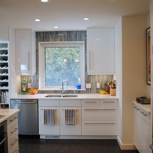 This is an example of a modern l-shaped eat-in kitchen in Edmonton with an undermount sink, flat-panel cabinets, white cabinets, quartz benchtops, blue splashback, glass tile splashback, stainless steel appliances, linoleum floors and a peninsula.