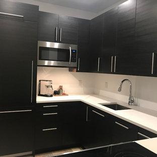 Bild på ett avskilt, litet funkis vit vitt u-kök, med en undermonterad diskho, släta luckor, svarta skåp, bänkskiva i kvarts, vitt stänkskydd, integrerade vitvaror, laminatgolv och beiget golv