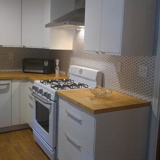 Mittelgroße Moderne Wohnküche ohne Insel in U-Form mit Unterbauwaschbecken, flächenbündigen Schrankfronten, weißen Schränken, Arbeitsplatte aus Holz, Küchenrückwand in Weiß, Rückwand aus Mosaikfliesen, weißen Elektrogeräten, hellem Holzboden und braunem Boden in Austin