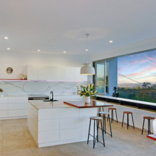 Design ideas for a large contemporary l-shaped open plan kitchen in Sunshine Coast with with island, flat-panel cabinets, white cabinets, white splashback, white benchtop, marble benchtops, marble splashback, stainless steel appliances, a single-bowl sink, porcelain floors and grey floor.