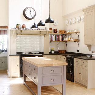 ウエストミッドランズのカントリー風おしゃれなキッチン (シェーカースタイル扉のキャビネット、御影石カウンター、白いキッチンパネル、サブウェイタイルのキッチンパネル、トラバーチンの床、黒い調理設備) の写真