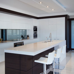 Diseño de cocina moderna con fregadero bajoencimera, armarios con paneles lisos, puertas de armario blancas, salpicadero verde, una isla, encimera de cuarzo compacto, salpicadero con efecto espejo y encimeras blancas