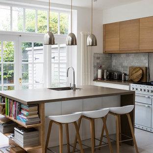 ロンドンのトランジショナルスタイルのおしゃれなアイランドキッチン (フラットパネル扉のキャビネット、中間色木目調キャビネット、グレーのキッチンパネル、サブウェイタイルのキッチンパネル、白い調理設備、アンダーカウンターシンク、トラバーチンの床) の写真