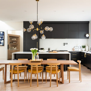 Large contemporary l-shaped eat-in kitchen in Calgary with an undermount sink, flat-panel cabinets, black cabinets, quartzite benchtops, white splashback, stainless steel appliances, light hardwood floors, with island, brown floor and white benchtop.