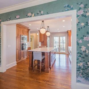 ニューヨークの大きいトラディショナルスタイルのおしゃれなキッチン (エプロンフロントシンク、シェーカースタイル扉のキャビネット、中間色木目調キャビネット、白いキッチンパネル、サブウェイタイルのキッチンパネル、シルバーの調理設備の、無垢フローリング) の写真