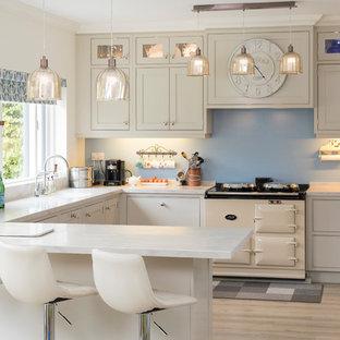 Foto de cocina clásica, de tamaño medio, abierta, con armarios estilo shaker, puertas de armario beige, salpicadero azul, electrodomésticos de colores, suelo de madera clara y suelo beige