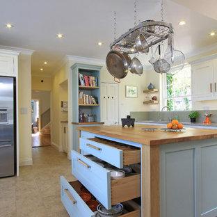 ハンプシャーのヴィクトリアン調のおしゃれなキッチン (シェーカースタイル扉のキャビネット、シルバーの調理設備の、木材カウンター、青いキャビネット) の写真