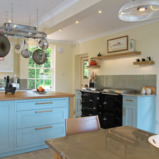 Inspiration for a classic kitchen/diner in Hampshire with wood worktops, shaker cabinets, blue cabinets and black appliances.
