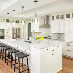 Photo of a large traditional l-shaped open plan kitchen in Detroit with an undermount sink, shaker cabinets, white cabinets, quartz benchtops, grey splashback, stone tile splashback, stainless steel appliances, medium hardwood floors, with island, brown floor, grey benchtop and coffered.