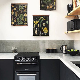 Photo of a small contemporary l-shaped open plan kitchen in Other with a drop-in sink, flat-panel cabinets, black cabinets, concrete benchtops, grey splashback, black appliances, painted wood floors, no island, white floor and grey benchtop.