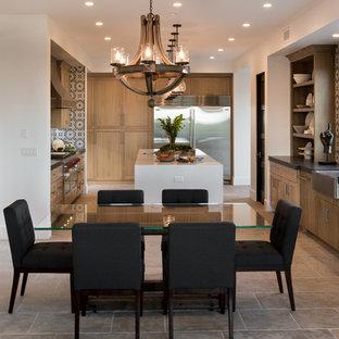 オレンジカウンティの中サイズのトランジショナルスタイルのおしゃれなキッチン (エプロンフロントシンク、落し込みパネル扉のキャビネット、中間色木目調キャビネット、御影石カウンター、青いキッチンパネル、セメントタイルのキッチンパネル、シルバーの調理設備、セラミックタイルの床、ベージュの床、黒いキッチンカウンター) の写真