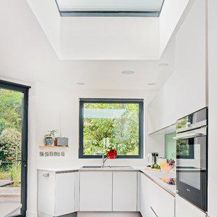 ロンドンの中くらいのコンテンポラリースタイルのおしゃれなL型キッチン (ドロップインシンク、フラットパネル扉のキャビネット、白いキャビネット、緑のキッチンパネル、人工大理石カウンター、ガラス板のキッチンパネル、クッションフロア) の写真