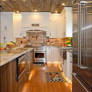 ニューヨークの広いトランジショナルスタイルのおしゃれなキッチン (エプロンフロントシンク、白いキャビネット、御影石カウンター、ベージュキッチンパネル、レンガのキッチンパネル、シルバーの調理設備、ラミネートの床、茶色い床、マルチカラーのキッチンカウンター、塗装板張りの天井) の写真