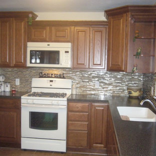 Example of a small classic l-shaped ceramic floor eat-in kitchen design in Milwaukee with an integrated sink, raised-panel cabinets, medium tone wood cabinets, laminate countertops, multicolored backsplash, glass tile backsplash, white appliances and no island