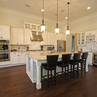 Large traditional eat-in kitchen photos - Example of a large classic l-shaped dark wood floor eat-in kitchen design in Miami with white cabinets, granite countertops, white backsplash, subway tile backsplash, stainless steel appliances and an island