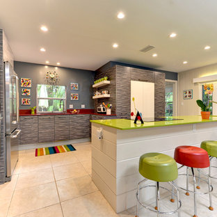 他の地域の大きいエクレクティックスタイルのおしゃれなキッチン (アンダーカウンターシンク、フラットパネル扉のキャビネット、グレーのキャビネット、人工大理石カウンター、シルバーの調理設備の、セラミックタイルの床、ベージュの床、緑のキッチンカウンター) の写真