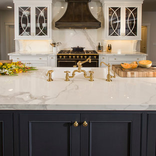 Photo of a large traditional l-shaped kitchen in Cincinnati with a farmhouse sink, glass-front cabinets, white cabinets, quartz benchtops, white splashback, stone slab splashback, panelled appliances, dark hardwood floors and multiple islands.