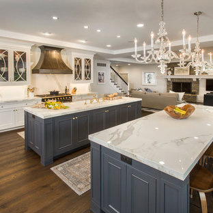 Design ideas for a large traditional galley open plan kitchen in Cincinnati with a farmhouse sink, quartz benchtops, white splashback, stone slab splashback, dark hardwood floors, multiple islands, white cabinets, black appliances and recessed-panel cabinets.