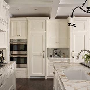Ejemplo de cocina en U, clásica renovada, grande, abierta, con fregadero de un seno, armarios con paneles lisos, puertas de armario blancas, encimera de mármol, salpicadero blanco, salpicadero de azulejos de cerámica, electrodomésticos con paneles y suelo de madera oscura