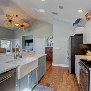 Bild på ett mellanstort maritimt linjärt kök med öppen planlösning, med en rustik diskho, skåp i shakerstil, vita skåp, bänkskiva i koppar, blått stänkskydd, stänkskydd i keramik, rostfria vitvaror, bambugolv, en köksö och brunt golv