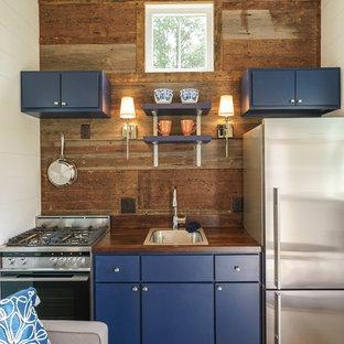 Foto di una piccola cucina lineare classica con lavello da incasso, ante lisce, ante blu, top in legno, elettrodomestici in acciaio inossidabile, parquet scuro e nessuna isola
