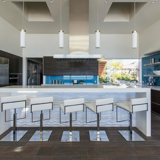 Contemporary kitchen remodeling - Example of a trendy brown floor kitchen design in San Luis Obispo with flat-panel cabinets, brown cabinets, blue backsplash, glass sheet backsplash, stainless steel appliances, an island and white countertops
