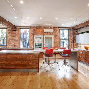 ニューヨークの大きいインダストリアルスタイルのおしゃれなキッチン (アンダーカウンターシンク、フラットパネル扉のキャビネット、中間色木目調キャビネット、コンクリートカウンター、赤いキッチンパネル、シルバーの調理設備、無垢フローリング) の写真