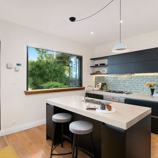 Photo of a contemporary single-wall kitchen in Sydney with a double-bowl sink, flat-panel cabinets, black cabinets, subway tile splashback, stainless steel appliances, medium hardwood floors, with island, brown floor, solid surface benchtops, grey splashback and white benchtop.