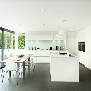 Design ideas for a large modern single-wall eat-in kitchen in Hampshire with flat-panel cabinets, white cabinets, grey floor, an undermount sink, solid surface benchtops, grey splashback, glass sheet splashback, stainless steel appliances and with island.
