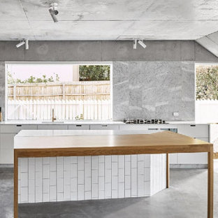 Photo of a beach style open plan kitchen in Brisbane with a single-bowl sink, flat-panel cabinets, white cabinets, grey splashback, concrete floors, with island, grey floor and grey benchtop.