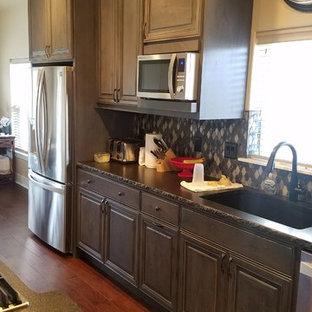 他の地域の中くらいのインダストリアルスタイルのおしゃれなキッチン (アンダーカウンターシンク、レイズドパネル扉のキャビネット、濃色木目調キャビネット、御影石カウンター、黒いキッチンパネル、ガラスタイルのキッチンパネル、シルバーの調理設備、無垢フローリング、赤い床、黒いキッチンカウンター) の写真