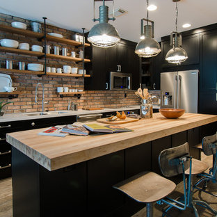 Small industrial l-shaped eat-in kitchen in Miami with a double-bowl sink, shaker cabinets, black cabinets, wood benchtops, stainless steel appliances, with island, red splashback, brick splashback, light hardwood floors, brown floor and white benchtop.