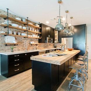 Ejemplo de cocina urbana, pequeña, con fregadero de doble seno, armarios estilo shaker, puertas de armario negras, encimera de cuarzo compacto, electrodomésticos de acero inoxidable, suelo vinílico y una isla